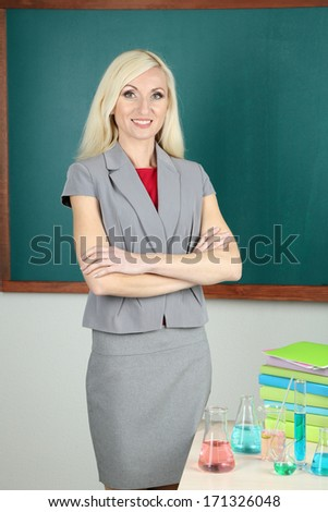 Chemistry teacher standing near table with tubes on blackboard background