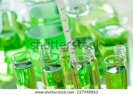 Chemists are measuring the temperature of the solution in a test tube in a laboratory