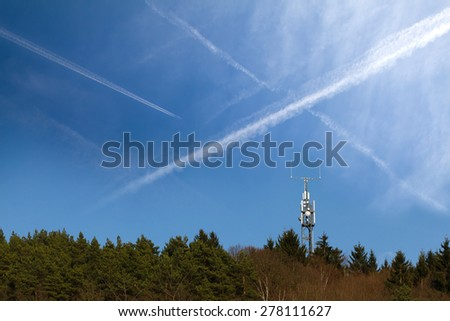 Chemtrails on a blue sky above a radio mast in the forest.