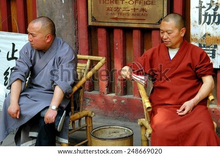Chengdu, China - April 25, 2005:  Two Buddhist monks sitting in bamboo chairs in front of the Wenshu Temple at the Manjursi Monastery