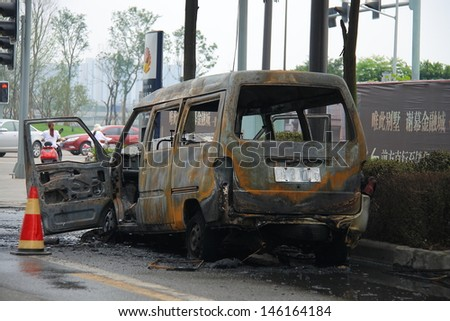 CHENGDU, CHINA - JULY 6: One burned car is abandoned on the road side after the traffic accident on July 6, 2013, Chengdu, Sichuan, China