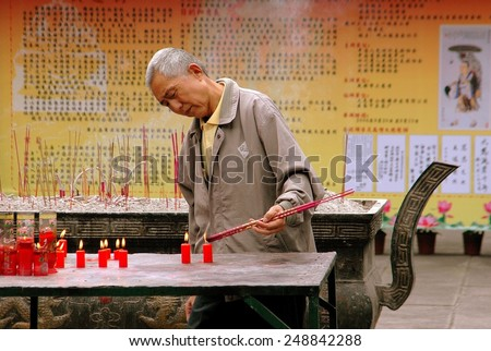 Chengdu, China - September 20, 2006:  An elderly Chinese man lighting incense sticks from burning red candles at the Da Ci Buddhist Temple - stock photo