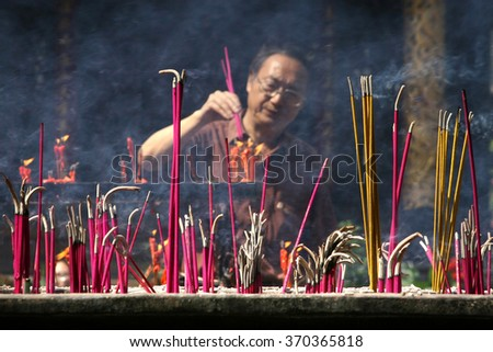 CHENGDU - JAN 23: Chinese man burning incense during Chinese New Year festival on January 23, 2012 in Chengdu, China. Chinese New Year is the longest and most important festivity in China. - stock photo