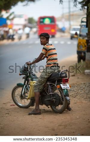 CHENNAI, INDIA-FEBRUARY 13: Boy on a motorcycle on February 13, 2013 in Chennai, India. Boy on a motorcycle on the streets of Chennai. - stock photo