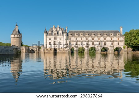 Chenonceau castle, built over the Cher river , Loire Valley,France, view from the river, on gradient blue sky background. - stock photo