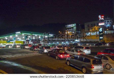CHERAS, KUALA LUMPUR, MALAYSIA-OCTOBER 1, 2014: Cars queue up at a local pump station in Alam Damai, Cheras. In order to reduce budget deficit, Malaysian government reduce fuel subsidies gradually. - stock photo
