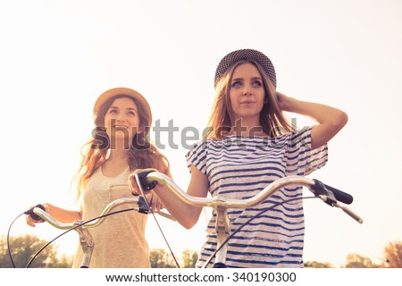 cherful  happy girls with hat ride bicycles on the park - stock photo