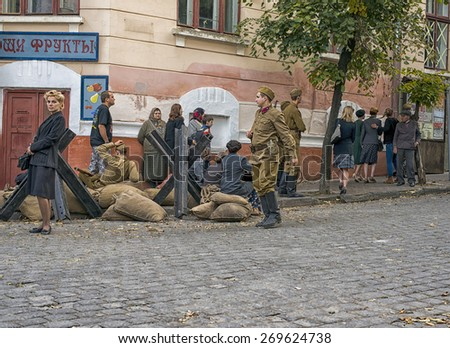 "CHERNIVTSI, UKRAINE - AUG 29, 2014: People working during shooting  the film ""According to the laws of war"". Location filming - st.""Ukrainian"" turn on st. ""Chelyuskintsev"" in Chernivtsi.. - stock photo"