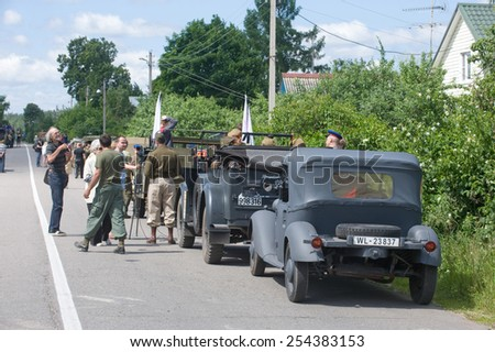 "CHERNOGOLOVKA, MOSCOW REGION, RUSSIA - JUNE 21, 2013: A column of military retro cars is on the side of the road, the 3rd international meeting of ""Motors of war"" near the city Chernogolovka"