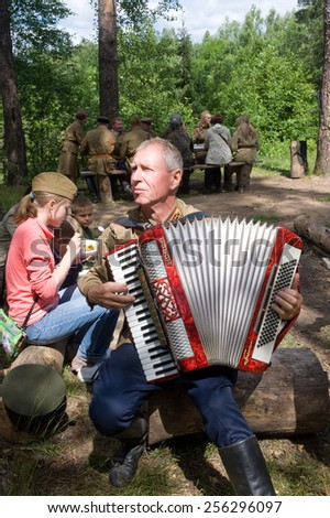 "CHERNOGOLOVKA, MOSCOW REGION, RUSSIA - JUNE 21, 2013: Accordionist, stopping to rest in the forest, 3rd international meeting ""Motors  of war"" near the city Chernogolovka, Moscow region"