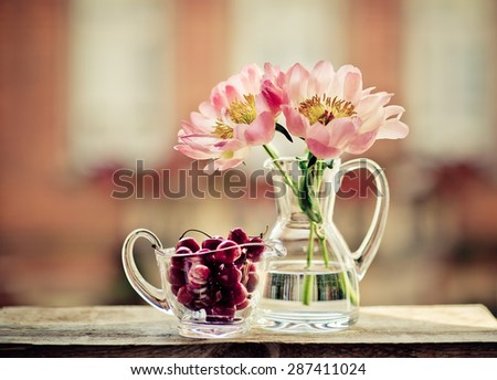 Cherries and Peony Flowers in front of Window - stock photo