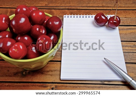 Cherries fruit and empty notepad on table