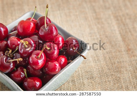 Cherries in a bowl on fabric bag