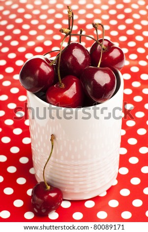 Cherries in a cup on polka dot background - stock photo