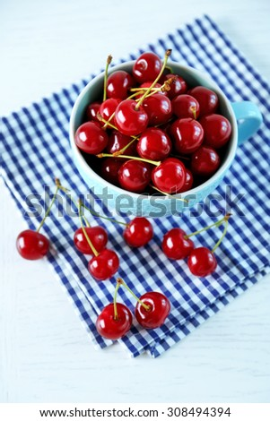 Cherries in mug on table, on light background