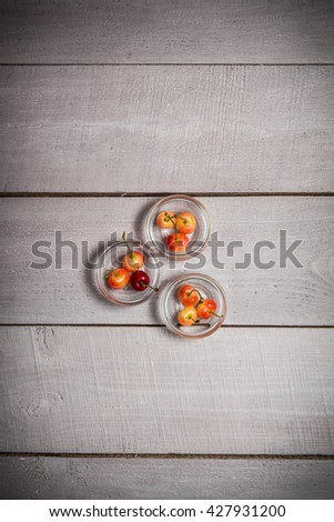 cherries in the saucer on a white wooden background, juicy, ripe, berry-sized portions on white boards  - stock photo