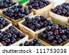 Cherries in wooden baskets at market - stock photo