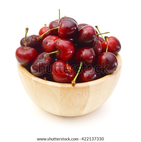 Cherries isolated in wooden bowl on white