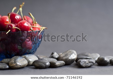 cherries on black background and stones