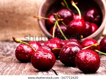 Cherries on wooden table with water drops macro background - stock photo