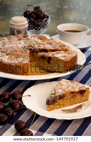 Cherry Almond Cake with fresh cherries in bowl, coffee and blue striped table clooth