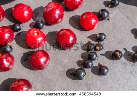 Cherry and black currant. Fresh healthy food. Summer berries background. Cherry and black currant background. Fresh berries on dark background. Red cherries and black currants scattered on table.