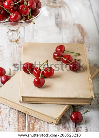 Cherry and old books on a wooden table - stock photo