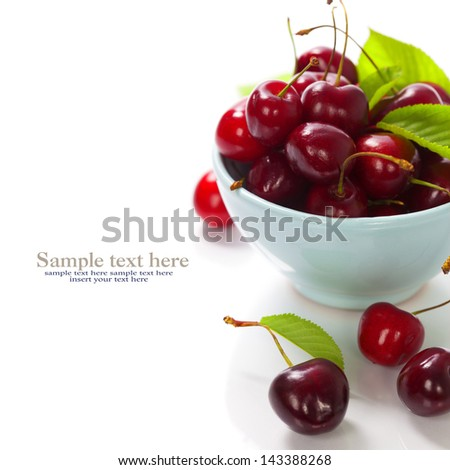 cherry berries in blue bowl. With easy removable sample text - stock photo