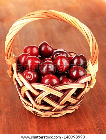 Cherry berries in wicker basket on wooden table close-up