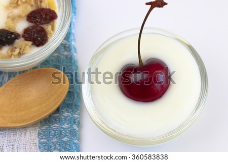 Cherry berry in Natural low-fat yogurt with muesli and banana, raisin in the glass cup.