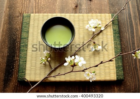Cherry blossoms and green tea on the Japanese tatami mat - stock photo