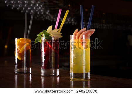 Cherry bomb, screwdriver and cuba libre cocktails in a tall glasses on the dark background. Shallow DOF - stock photo