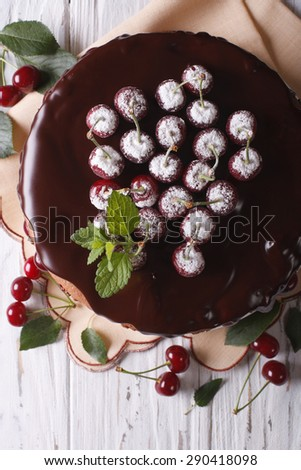 Cherry cake with chocolate frosting on a table close-up. vertical top view  - stock photo