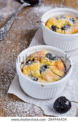 Cherry Clafoutis in a baking pan. Decorations - fresh cherries, vintage spoon, powdered sugar. - stock photo