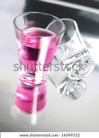 Cherry cocktail shot on silver floor - stock photo