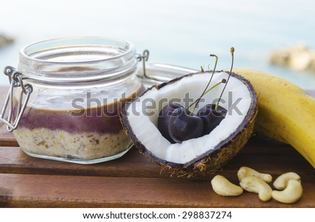 Cherry coconut banana overnight oats with cracked open coco, banana, cashews mixed with chia seeds and cherry cream in a mason jar, on a tropical sea background. Healthy fitness breakfast oatmeal. - stock photo