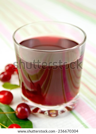 Cherry compote in a low glass on a background of a linen tablecloth