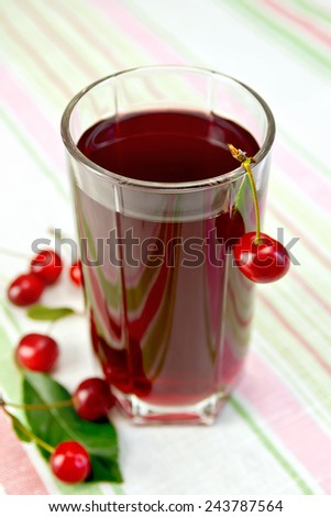 Cherry compote in a tall glass on a background of a linen tablecloth