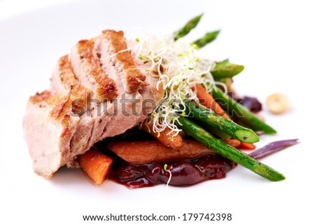 Cherry duck breast, with warm asparagus and baby carrot salad - stock photo
