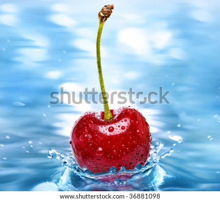 Cherry falls into the cold aqua water surface close up macro - stock photo