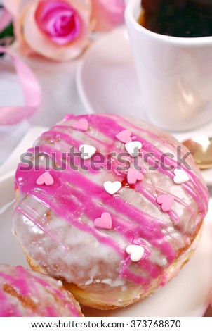 cherry filled donuts with icing and heart shaped sprinkles and cup of coffee for romantic valentine`s day - stock photo