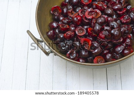 cherry fruits in a metal bowl on white wood table
