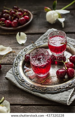 Cherry homemade liquor in a vintage glasses  on metal tray and cherries. Wooden background, selective focus. - stock photo