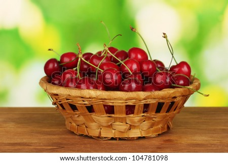 cherry in wicker bowl on wooden table on green background