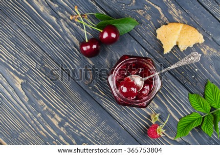 Cherry jam and raspberry in glass jars on wooden table. Top view - stock photo