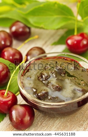 Cherry jam in a glass bowl and fresh berries - stock photo