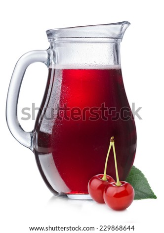 Cherry juice in a misted pitcher. Full jug of sour cherry juice with cherries on foreground - stock photo