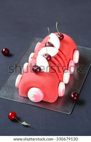 Cherry Lychee and Pistachio Yule Log Cake, decorated with macaron shells and red velvet spray, on a dark background. - stock photo