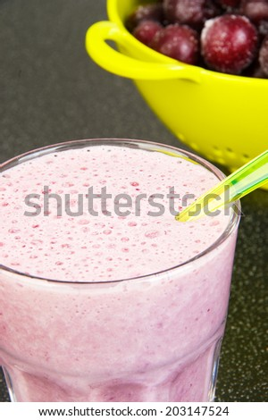 Cherry milk shake in a glass cup with a spoon and a light green colander with frozen cherries on a dark background - stock photo