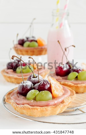 Cherry mini tarts with fruits and milk drink in bottle, white background - stock photo